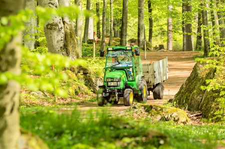 deere: RONNEBY, SWEDEN - May 11, 2015: Small John Deere compact utility tractor 2520 used in the forest on narrow path. Here seen with a trailer in surrounding beech forest.