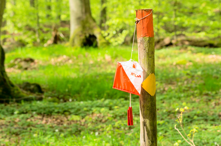 silva: RONNEBY, SWEDEN - May 11, 2015: Silva brand orientation control on trail marker in the forest. Silva is known for selling compasses and running watches. Editorial