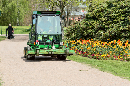 Ronneby, Sweden - May 11, 2015: John Deere grass cutting vehicle driving along gravel road in public park. Tulips and Rhododendron grow beside road.