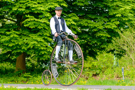 high powered: Solvesborg, Sweden - May 16, 2015: International Veteran Cycle Association (IVCA) 35th rally. Costume ride through public streets in town. Man on high wheeler.