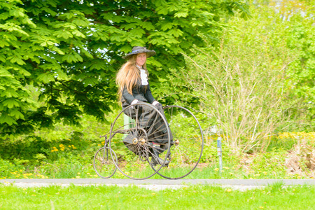 antique tricycle: Solvesborg, Sweden - May 16, 2015: International Veteran Cycle Association (IVCA) 35th rally. Costume ride through public streets in town. Woman on tricycle.