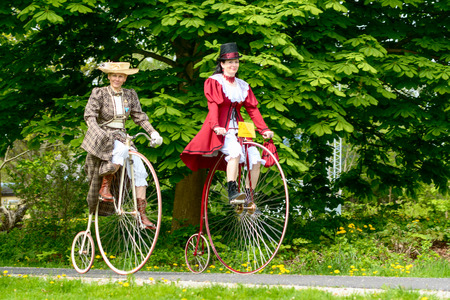 velocipede: Solvesborg, Sweden - May 16, 2015: International Veteran Cycle Association (IVCA) 35th rally. Costume ride through public streets in town. Two female on high wheelers.