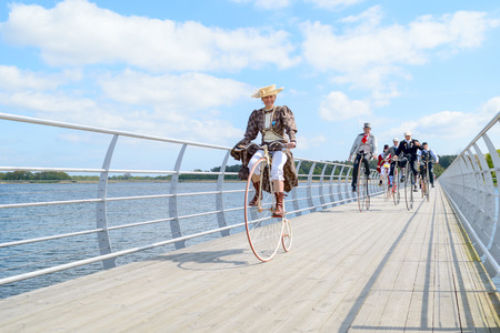chased: Solvesborg, Sweden - May 16, 2015: International Veteran Cycle Association (IVCA) 35th rally. Costume ride through public streets in town. Happy woman on penny-farthing chased by men. Editorial
