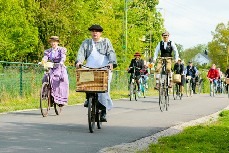 high powered: Solvesborg, Sweden - May 16, 2015: International Veteran Cycle Association (IVCA) 35th rally. Costume ride through public streets in town. Persons on old bikes.