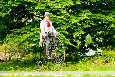 high powered: Solvesborg, Sweden - May 16, 2015: International Veteran Cycle Association (IVCA) 35th rally. Costume ride through public streets in town. Elegant man on penny-farthing.