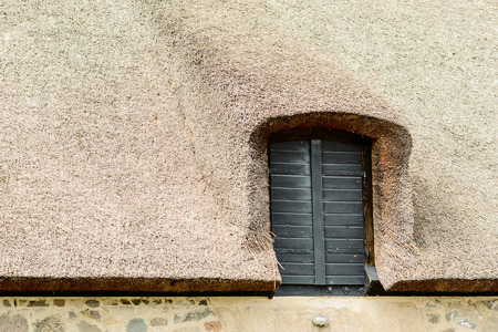 tightly: Tightly packed reed roof with black wooden hatch. Detail of traditional barn. Stock Photo