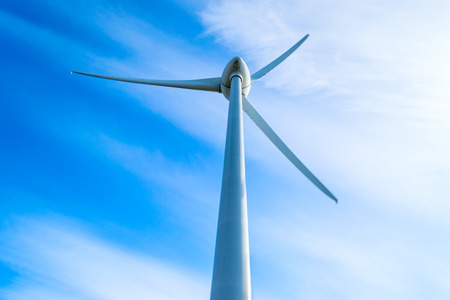 slight: Wind turbine with fine blue sky and white clouds in background. Slight movement visible on blades.