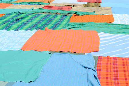 bedspread: Multicolored blankets on the ground. All spread out to form a large place to sit.