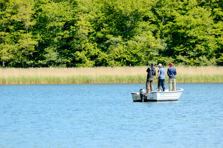 cast off: Almo, Sweden - June 11, 2015: Friends out fishing with rods in a boat near the coastline one fine summer day. Editorial