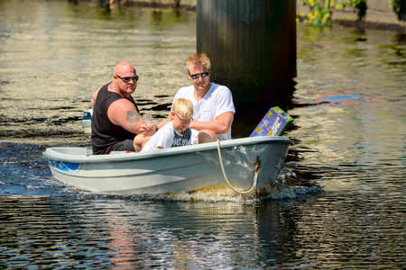 three persons: Ronneby, Sweden - June 13, 2015: Sillarodden, a public rowing contest from sea to town to sell herring. Three persons in small motor boat on the river seen face on. Editorial