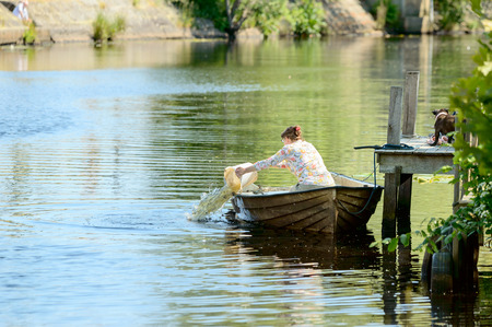 living idyll: Ronneby, Sweden - June 13, 2015: Unknown woman empty her boat from rainwater with a bucket. Dog stands on bridge waiting for her. Editorial