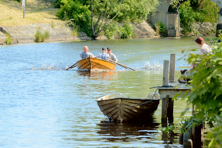 fortitude: Ronneby, Sweden - June 13, 2015: Sillarodden, a rowing contest from sea to town to sell herring. Five senior men struggle to gain speed.