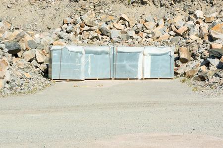 gravel pit: Plastic materials on pallets in gravel pit.