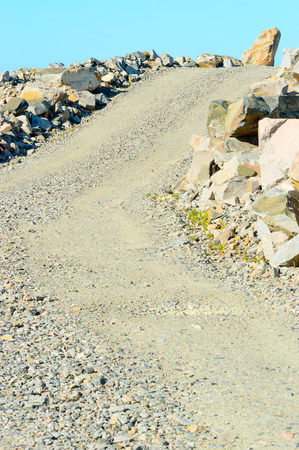 gravel pit: Dirt road in gravel pit with small slope up. Stock Photo