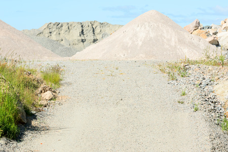 gravel pit: Small dirt road sloping up to gravel pit with gravel hills.