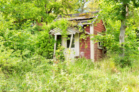 regain: Abandoned building where nature slowly take over again. Red facade with white corners.