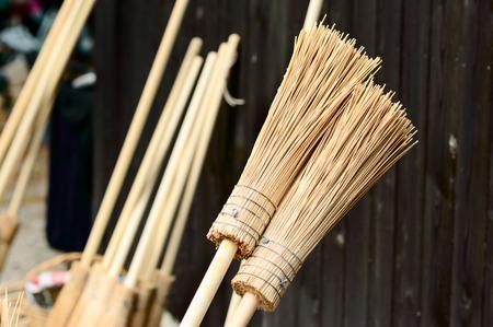 New handmade broomsticks leaning against dark wooden wall.