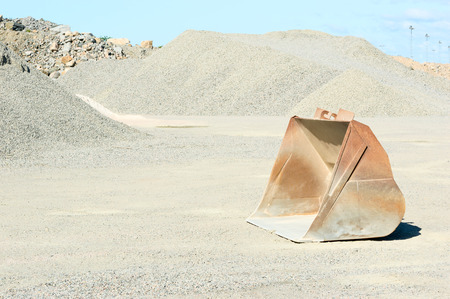 gravel pit: One empty loading bucket left in gravel pit after use.