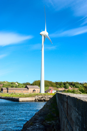 airstream: Wind turbine with fine blue sky and white clouds in background. Stone wall and water in front and some houses and forest in back. Stock Photo