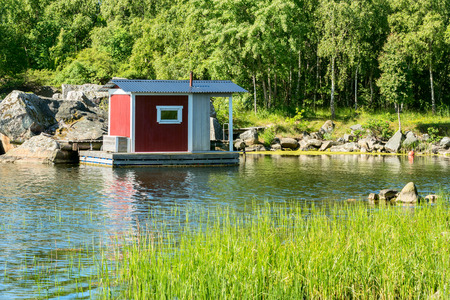 fishing cabin: Small fishing cabin on floating bridge in the sea. Green nature in surrounding area.