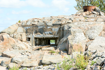 bunker: Old stone bunker ruin in the coastline. Small part of the sea is visible through opening in bunker. Stock Photo