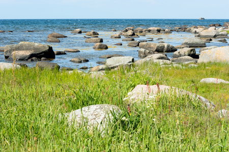 stretch out: Granite boulders stretch out into the sea with green vegetation on land. Open sea at horizon.
