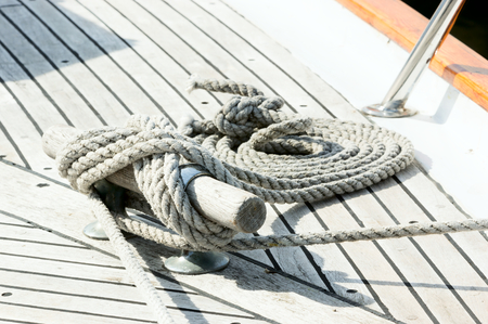gnarled: Old gnarled rope curled up on wooden deck on moored boat. Stock Photo