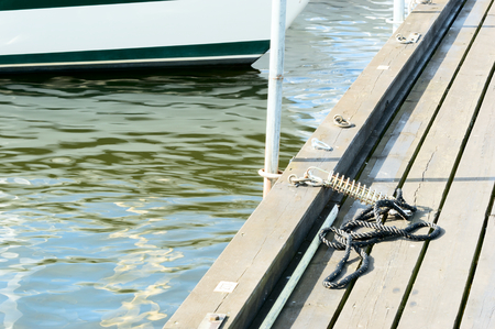 keel: Small rope curled up on wooden bridge on marina. Water and boat keel in background.