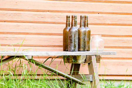 brown bottles: Old and dirty vintage brown bottles and a glass jar on an old weathered wooden bench outside red building with high grass in front.