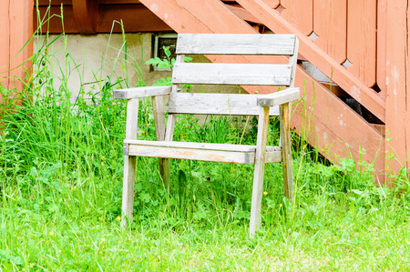 unpainted: Old weathered and unpainted wooden garden chair in high green grass outside red building.