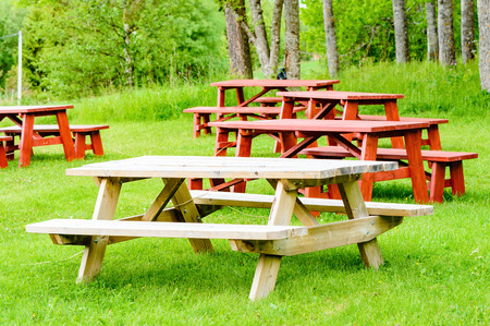 unpainted: Red and unpainted garden furniture on green grass with forest in background. Seat and table are connected and formes one unit. Stock Photo