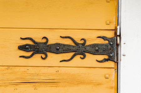 hinge: Black old iron hinge on old yellow wooden door.