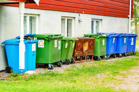 reprocess: Froso, Sweden - June 29, 2015: Lot of garbage bins on the backside of a restaurant. Wooden cabinet in center.