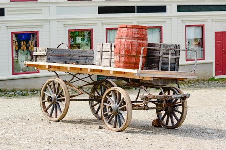 carreta madera: Carro de madera viejo cargado con barriles y troncos. Aqu� visto fuera de un edificio de la tienda de edad. Foto de archivo