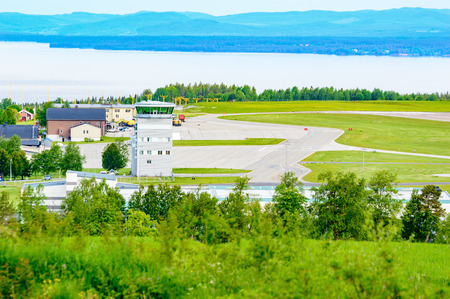 runways: Froso, Sweden - June 29, 2015: Froso airport seen from a distance and from higher ground. Control tower and runways, grass area. Forest in foreground and lake in back.