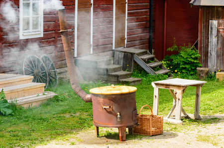 stove pipe: Boiling water in large stove for outdoor laundry. Smoke come out of chimney. Red wooden house in background. This is how it was done in the old times.