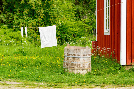 front  or back  yard: Laundry is hanging from a line outside a red wooden house.