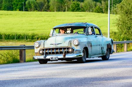 timeless: Ronneby, Sweden - June 26, 2015: Veteran car street cruise on public roads. Light green Chevrolet 2103 4 D sedan 1953