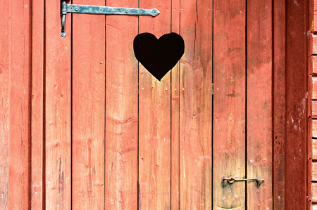 Outdoor toilet door with carved heart below iron hinge. Old traditional marking for outhouses in Scandinavia. Heart also serve as window or inspection hole.