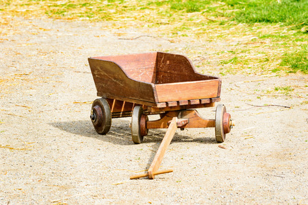 reinforced: Small wooden cart with metal reinforced wheels on gravel road.