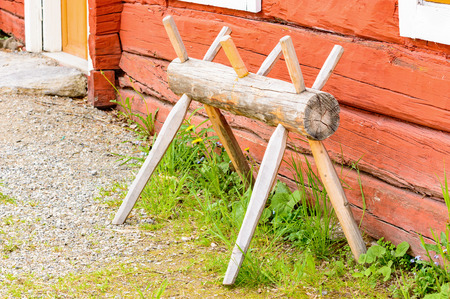 sawhorse: Old antique sawhorse in traditional style outside a red farm house.