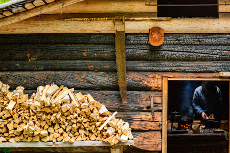 kindling: Woodsman cooking over open fire inside a cabin. Firewood and hand saw outside cabin. Walls are burnt instead of painted.