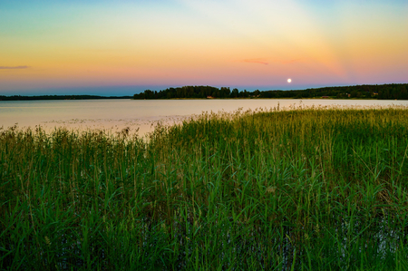 mood moody: Full moon over lake in late evening. Reeds in foreground and distant cabins on opposite shore. Calm water and fine sky. Stock Photo