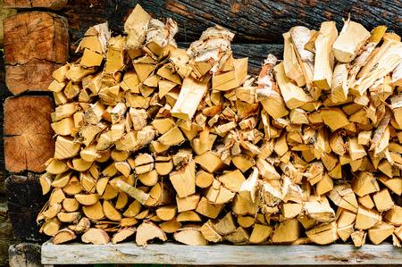 kindling: Pile of firewood or kindling on bench outside a cabin.
