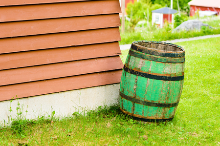 Green wooden barrel to collect rain water in. Slightly tilted and with small red cabins in background.