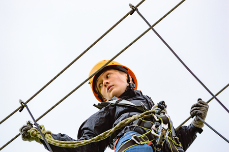 Teenage female in high altitude adventure. Fearless and brave she climbs and swings through the canopy in safty gear and harness.
