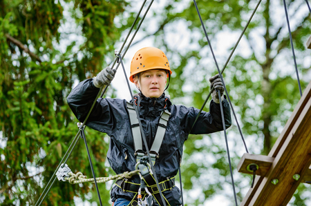 safty: Teenage female in high altitude adventure. Fearless and brave she climbs and swings through the canopy in safty gear and harness.
