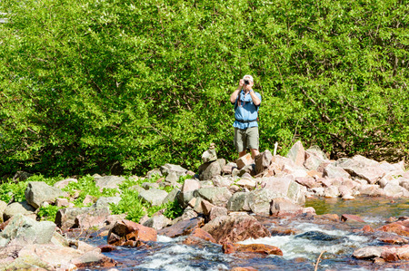shrubbery: Dalarna, Sweden – July 01, 2015: Unknown male tourist taking photo of river. He is standing on sharp rocks and has green shrubbery behind. River has some whitewater in front of him. Sunny day.