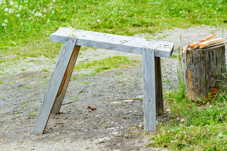 kindling: Slightly tilted wooden workbench with birch twigs on one end. Small part of log with kindling on top to the side. Ground is gravel and partly damp under bench. Grass in background. No person in image.