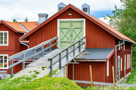 second floor: Wooden vehicle and animal ramp leading up to a house on second floor. Red farm building that uses both the upper and lower floor for storing animals and utensils. Ramp rests on part of roof. Stock Photo